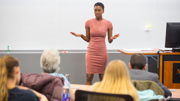 Maya Sudduth presenting her senior project to attendees inside Glass Hall on Dec. 5, 2017.