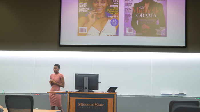 Maya Sudduth speaking while projection screen displays magazine covers that relate to her senior project.