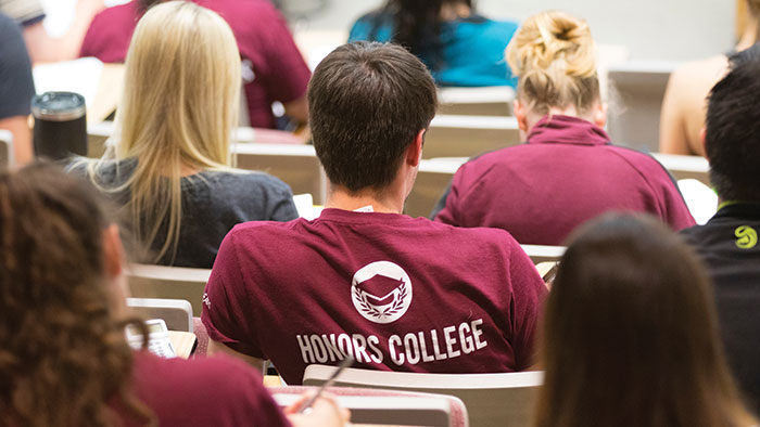 "The back of students sitting in a lecture hall; the back of one student's shirt says ""Honors College"""