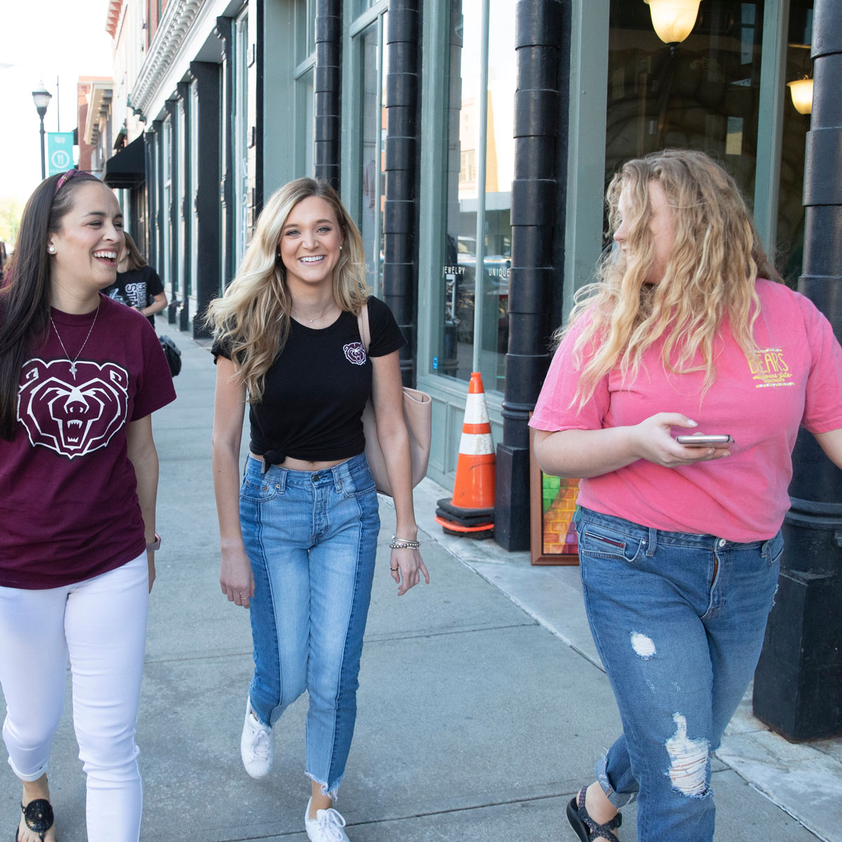 Three female students laugh as they walk downtown.