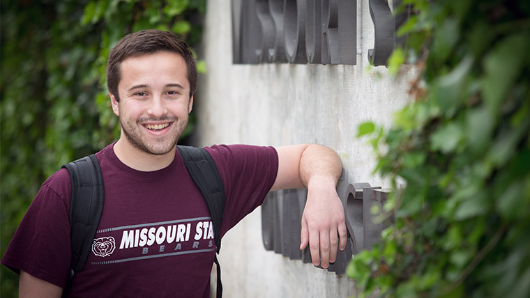 Smiling Missouri State student with backpack on the Missouri State campus.