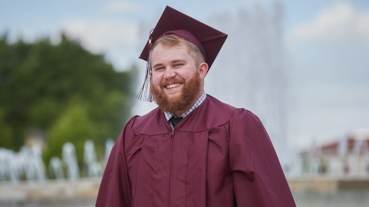 Smiling Missouri State graduate, in cap and gown, standing in front of John Q. Hammons Fountains.