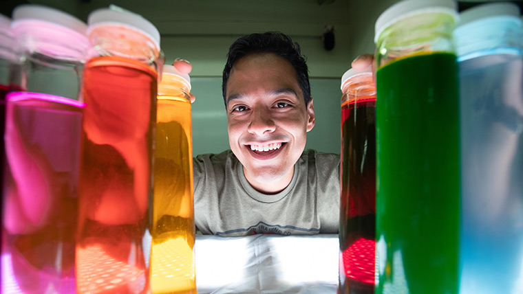 A Missouri State student standing behind beakers containing colorful solution.