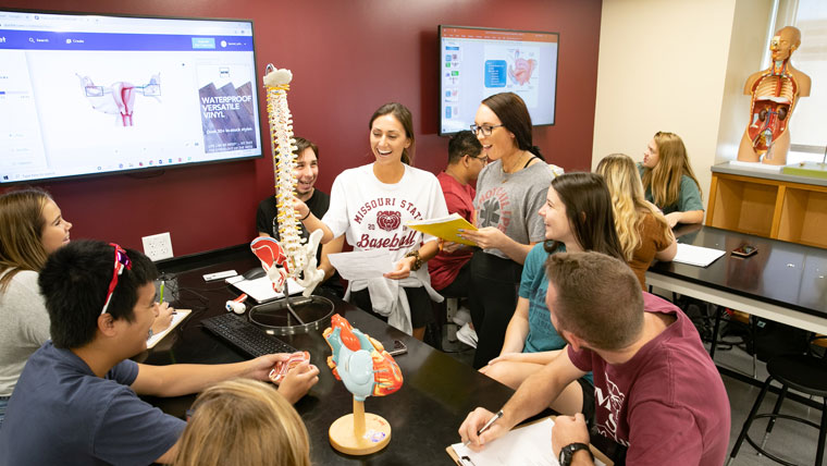 Missouri State students study with their instructor in a lab on campus.