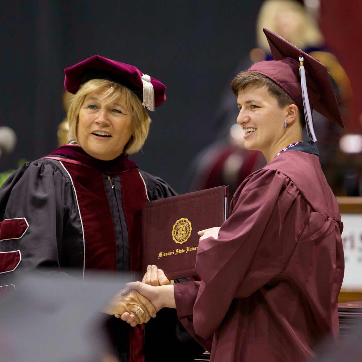 Graduating student shakes hand with Board of Governors member while accepting diploma.