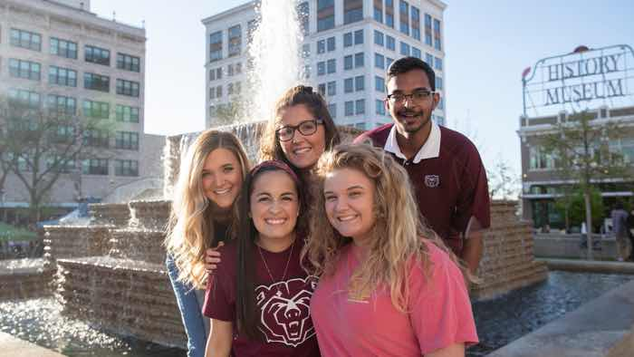 Group of students standing in front of a fountain with an urban background.