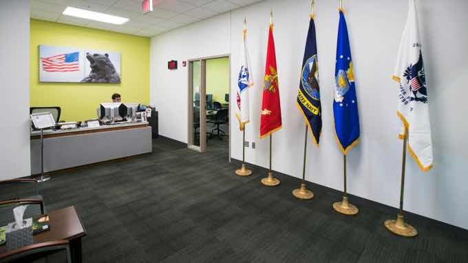 Office foyer with flags from each military branch.