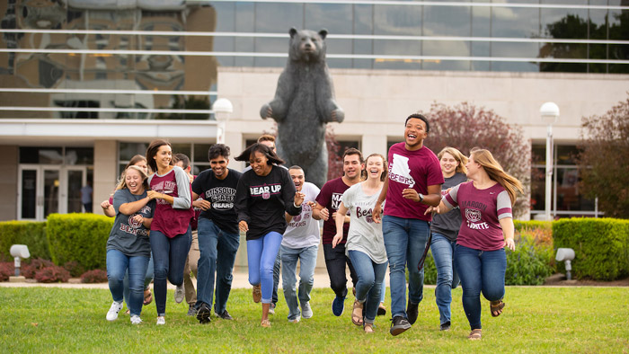 Students on campus with the PSU Bear in the background.