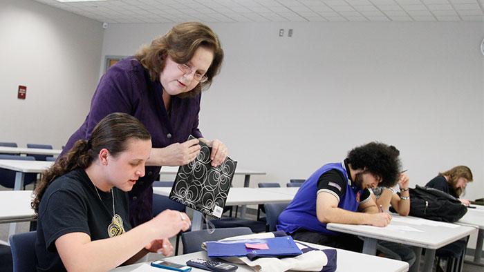 Professor assisting a student with her calculator.