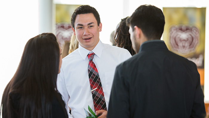 A student in business attires talks to others
