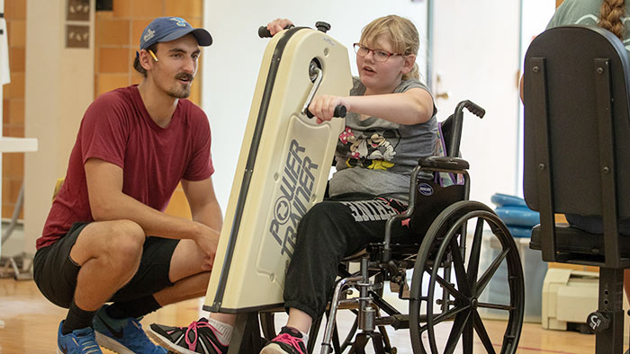 Kinesiology student working with child in adaptive physical education lab.