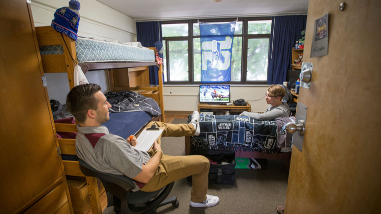 Two students sit in a residence hall room