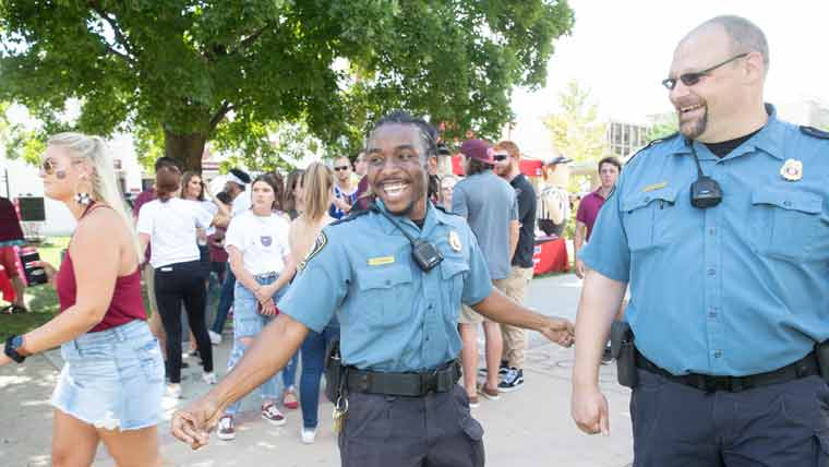 Two officers among a crowd of students at large event