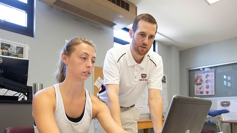 Kinesiology professor helping student.