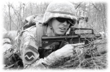 A black-and-white photo of a soldier in the brush