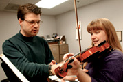 Student receiving violin instruction